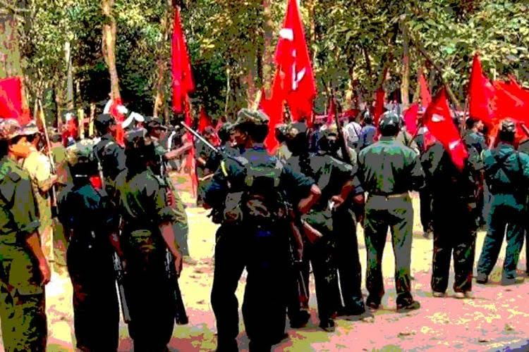 Maoists holding guns and flags in their hands